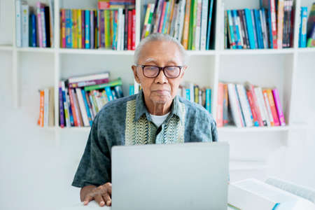 Elderly man working with a laptop computer while wearing glasses in the library with bookcase background