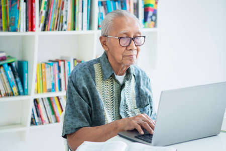 Old man with gray hair working with a laptop computer on the table in the library