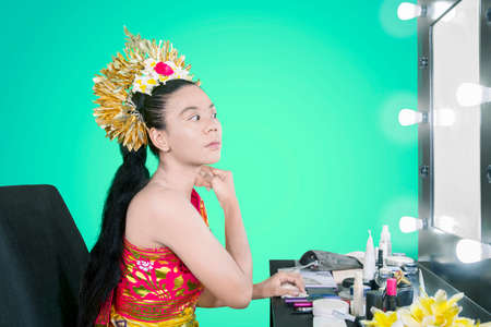 Young balinese dancer applying makeup on her face and neck with a sponge in makeup room