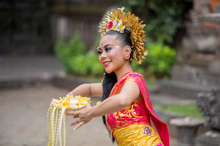 Attractive balinese pendet dancer performing in the temple while wearing traditional costume and holding flowers 版權商用圖片