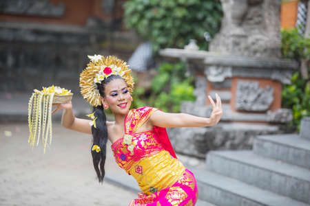 Beautiful female dancer carrying a bowl of flower petals while performing Pendet dance in the temple