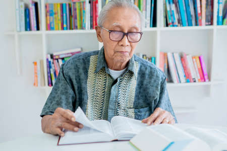Elderly man reading books on desk while wearing glasses in the library with bookshelf background Archivio Fotografico