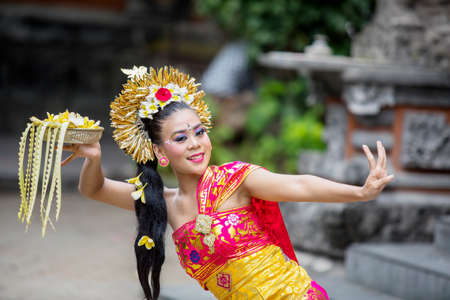 Young balinese pendet dancer dancing in the temple while smiling and holding flowers 版權商用圖片
