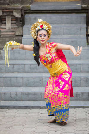 Female Pendet dancer dancing and carrying a bowl of flower petals at outdoor