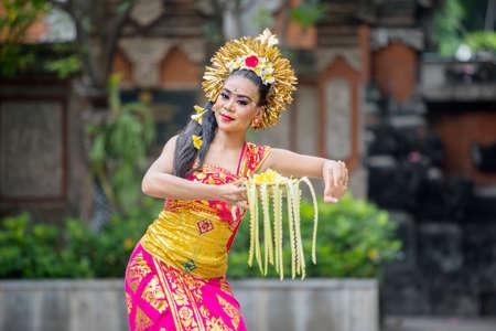 Beautiful dancer dancing Pendet dances with a bowl of flower petals at outdoor 版權商用圖片