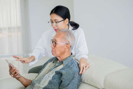 Happy senior man and his daughter using smartphone while sitting on the sofa in the living room at home Banco de Imagens