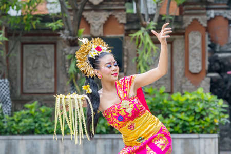 Balinese dancer showing a dance while carrying a bowl of flower petals in the temple 版權商用圖片