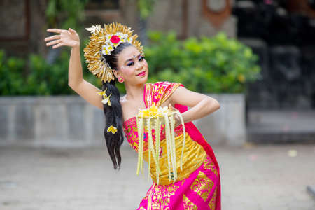 Picture of beautiful dancer dancing Pendet dances with a bowl of flower petals at outdoor