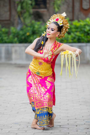 Picture of young Balinese dancer dancing Pendet dances with a bowl of flower petals at outdoor