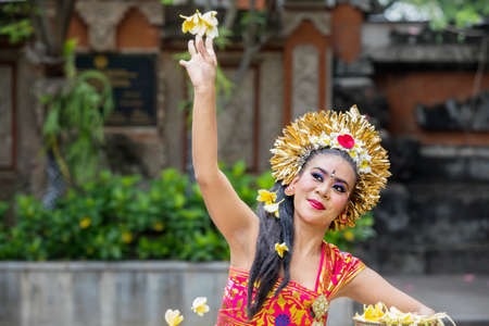 Female Pendet dancer performs while throwing frangipani flower in the temple 版權商用圖片