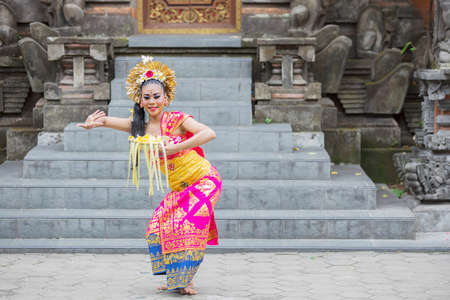 Female Pendet dancer carrying a bowl of flower petals while dancing front of a temple door