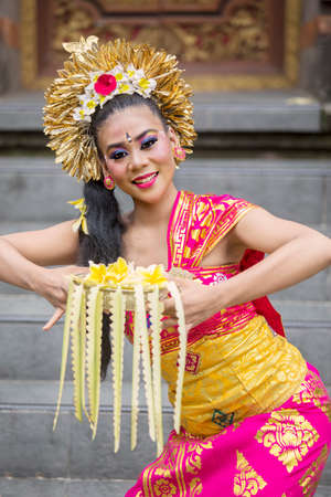 Pretty balinese dancer performing in the temple while holding frangipani flower