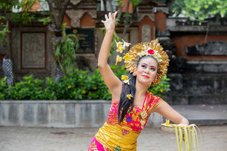 Picture of beautiful Pendet dancer performs while throwing frangipani flowers in the temple
