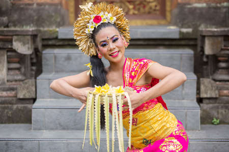 Attractive balinese dancer dancing in the temple while holding frangipani flowers and smiling at the camera