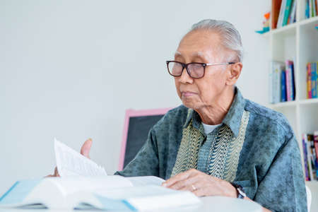 Senior man reading books on the table while wearing glasses in the library