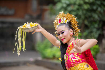 Pretty balinese pendet dancer dancing in the temple while holding flowers and wearing traditional clothes