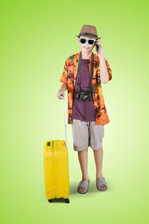 Full length of teenage boy talking on a mobile phone while holding a luggage in the studio