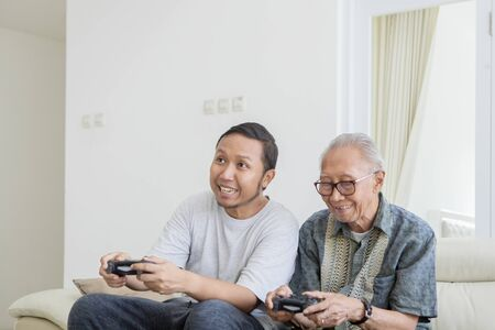 Happy elderly man playing video games with his son while sitting on the sofa in the living room at home