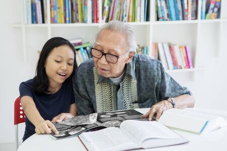 Senior man and his granddaughter reading books together on the table in the library