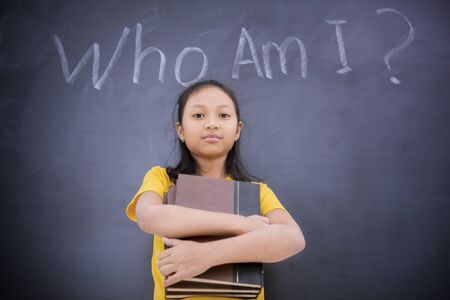 Picture of schoolgirl holding books while standing in the class with text of Who Am I? on a blackboard