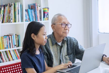 Little girl and her grandfather using a laptop computer together on the table in the library with bookcase background 版權商用圖片