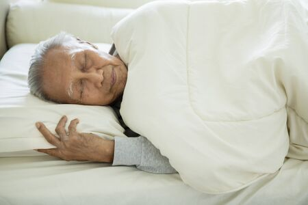 Picture of elderly man wrapped with a blanket while sleeping on a bed. Shot in the bedroom Фото со стока