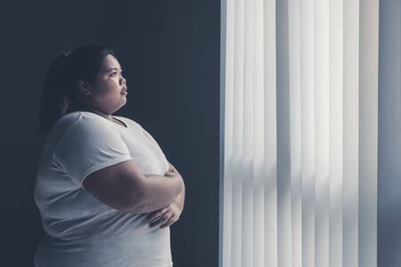 Picture of overweight woman looking out the window while standing in the dark room