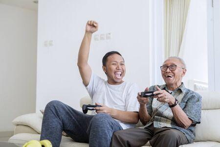 Joven emocionado jugando videojuegos con su padre y sentado en el sofá en casa Foto de archivo