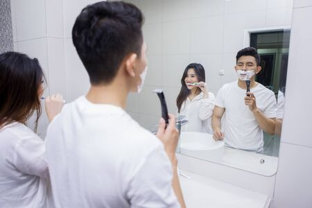 Picture of Asian young man shaving his beard and his wife brushing teeth in the bathroom