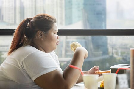Side view of overweight woman enjoying leisure time with a mobile phone and ice cream cone in the cafe