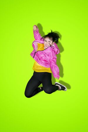 Cheerful hip-hop dancer jumping and dancing in the studio with green screen background