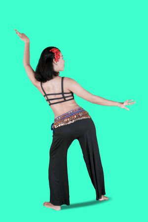 Back view of belly dancer doing dance exercises in the studio with green tosca background