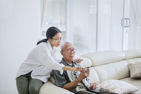 Picture of elderly man using a mobile phone with his daughter while sitting together on the couch