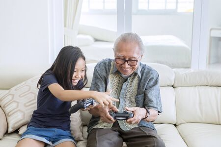 Happy old man using joystick while playing video games with his granddaughter and sitting on the sofa. Shot at home