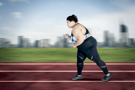 Picture of obese woman wearing sportswear while sprinting exercises on the track with fast motion blur Stock Photo