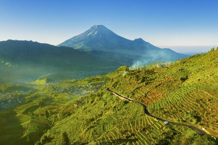 Beautiful scenery of Dieng Plateau with farmland and road in Central Java, Indonesia