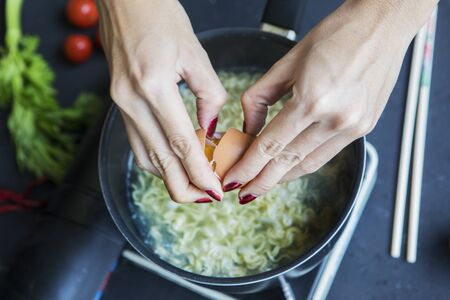 Hands of young woman cracking an egg into the boiled noodle in a pan