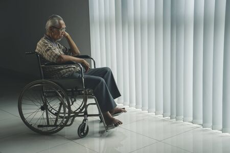 Picture of elderly man looks sad while sitting in the wheelchair near the window in the retirement home