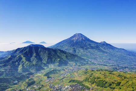Aerial view of Dieng plateau with village and Sindoro mountain in Central Java, Indonesia Stok Fotoğraf - 127969741