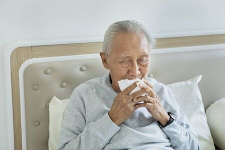 Portrait of senior man sneezing with tissues in his hands while lying on the bed Stock Photo