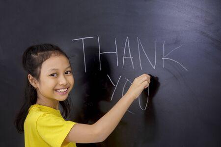 Concepto de apreciación del maestro. Estudiante de la escuela primaria femenina escribiendo texto de agradecimiento en la pizarra en el aula
