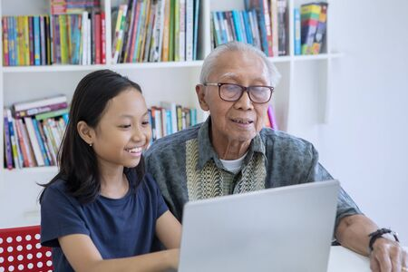 Old man teaching his granddaughter to use a laptop computer while sitting in the library with bookcase background 写真素材