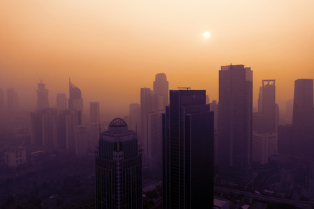JAKARTA - Indonesia. July 15, 2019: Jakarta cityscape covered by dust smog at sunset time