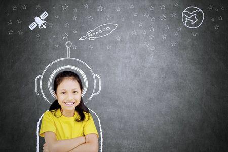 Foto van zelfverzekerd schoolmeisje dat naar de camera lacht terwijl ze zich voorstelt een astronaut te zijn Stockfoto