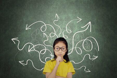 Studentessa di scuola elementare che pensa qualcosa mentre sta in piedi con i simboli caotici della freccia Archivio Fotografico