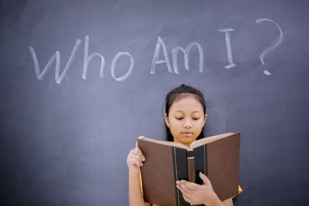 Female elementary school student reading a book while standing with text of Who Am I in the blackboard