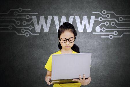 Imagen de una estudiante de escuela primaria que usa una computadora portátil para navegar por Internet en línea con el icono de www Foto de archivo