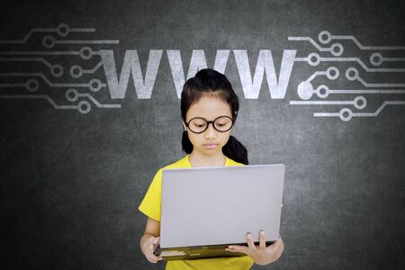 Picture of female elementary school student using a laptop computer for browsing internet online with www icon Imagens