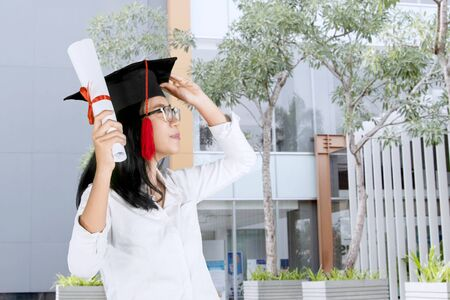 Side view of young woman celebrating her graduation while wearing a graduation cap and holding a diploma Stok Fotoğraf