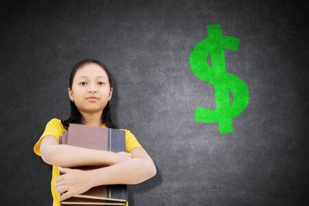 Female elementary school student holding books while standing with a dollar sign in the classroom